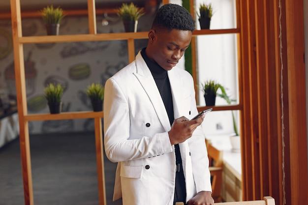 Homem negro em uma jaqueta branca de pé com um telefone