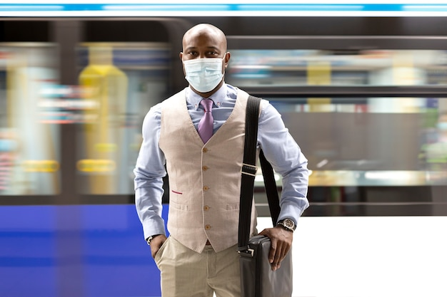 Homem negro empreendedor usando uma máscara facial, caminhando perto de um trem do metrô em movimento.