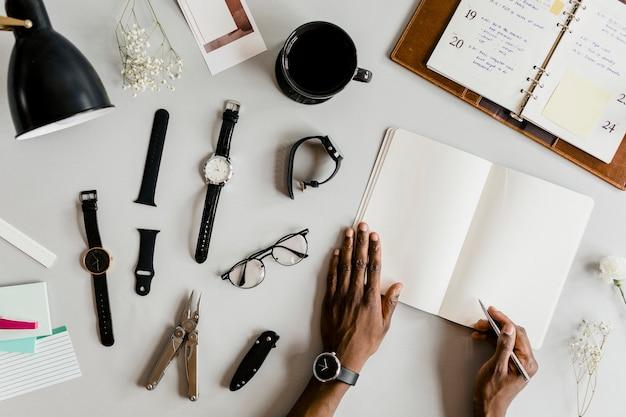 Homem negro escrevendo em um caderno cercado de itens essenciais do dia a dia