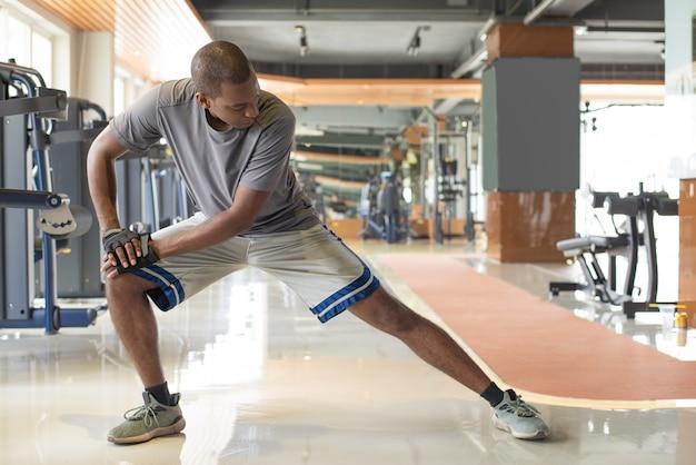 Homem negro, esticando a perna no ginásio