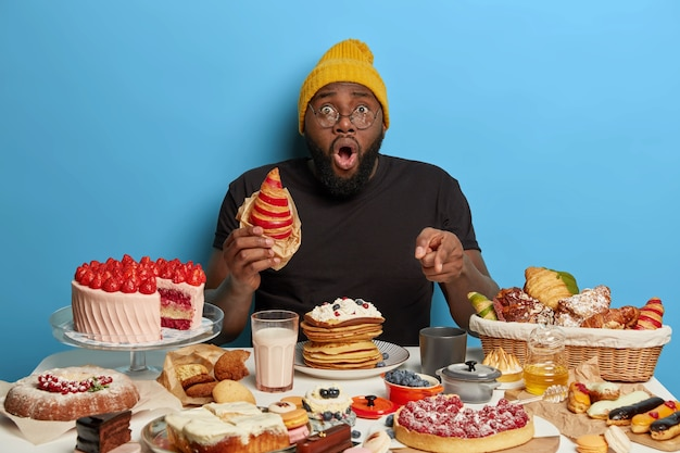 Homem negro estupefato come um croissant saboroso, aponta para uma mesa cheia de sobremesas doces deliciosas, usa chapéu e camiseta, posa contra um fundo azul
