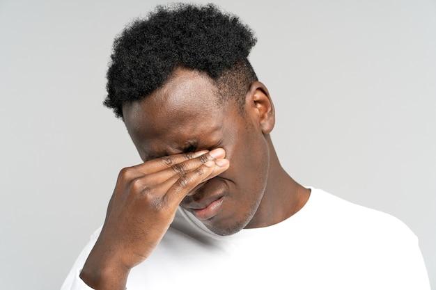 Homem negro exausto quer dormir esfregando os olhos e sente-se cansado depois do trabalho no laptop de excesso de trabalho