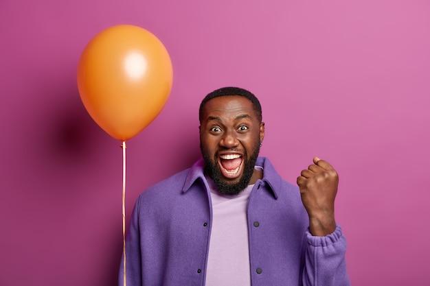 Homem negro feliz fecha o punho triunfante, comemora a conquista de novo emprego e promoção, faz festa corporativa com colegas, segura balão