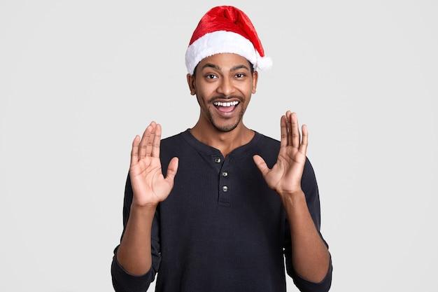 Homem negro feliz levanta as mãos e mostra as palmas das mãos com felicidade, usa chapéu de papai noel, sorri amplamente, mostra dentes brancos perfeitos