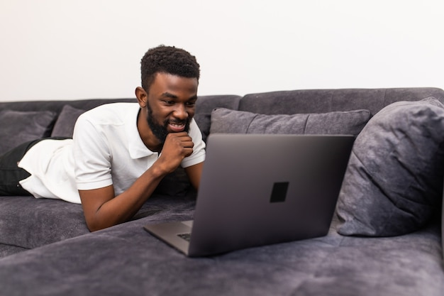 Homem negro feliz sentado no sofá-cama de sua casa trabalhando ou curtindo um filme da internet no laptop da sala de estar