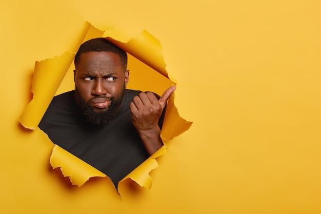 Homem negro frustrado e infeliz com um sorriso afetado, aponta para longe com um olhar desconfiado e nada impressionado, posa em um fundo de papel amarelo rasgado