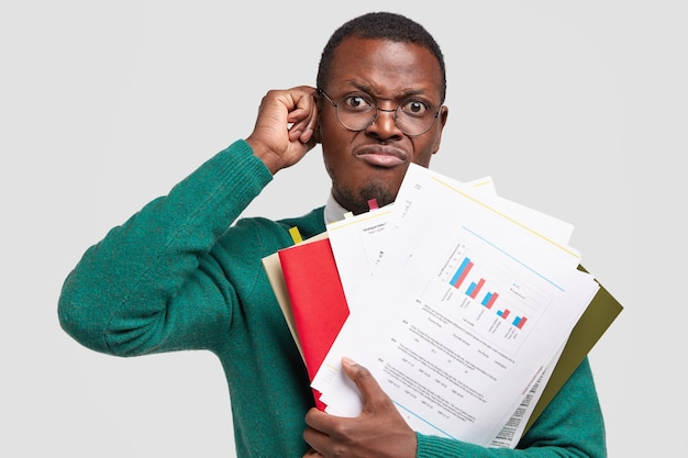 Homem negro insatisfeito prepara relatório contábil, segura papéis com informações, usa óculos para uma boa visão