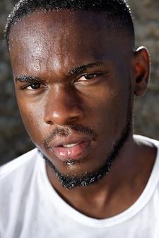 Homem negro jovem bonito com suor escorrendo pelo rosto