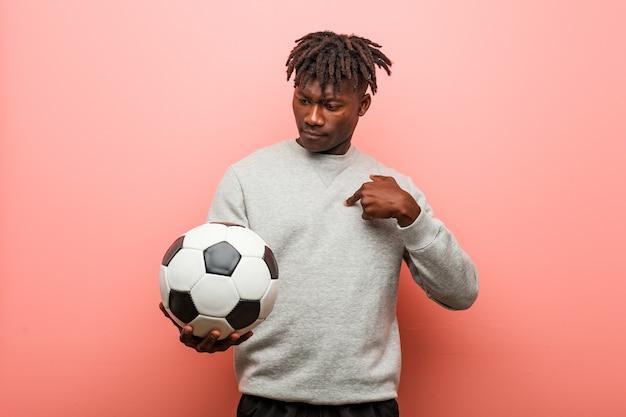 Homem negro jovem fitness segurando uma bola de futebol surpreso, apontando para si mesmo, sorrindo amplamente.