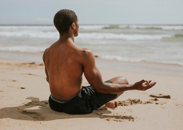 Homem negro meditando na praia