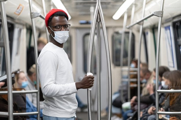 Homem negro milenar usa máscara facial como proteção, segura o corrimão no trem do metrô através de um guardanapo