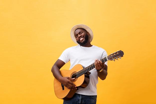 Homem negro muscular que joga a guitarra, calças de brim vestindo e camiseta de alças branca. isolar sobre fundo amarelo.