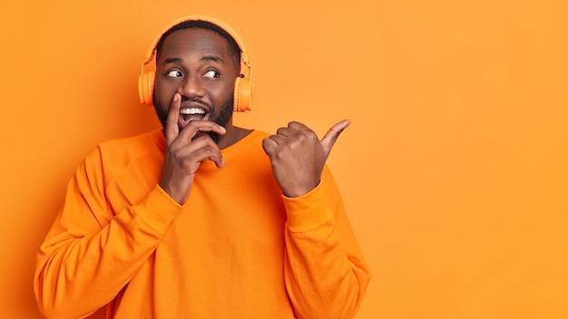 Homem negro não barbeado positivo com barba grossa aponta o polegar para longe em um espaço em branco e bom humor ouve trilha de áudio por meio de fones de ouvido vestidos com poses de jumper de mangas compridas contra uma parede laranja vívida