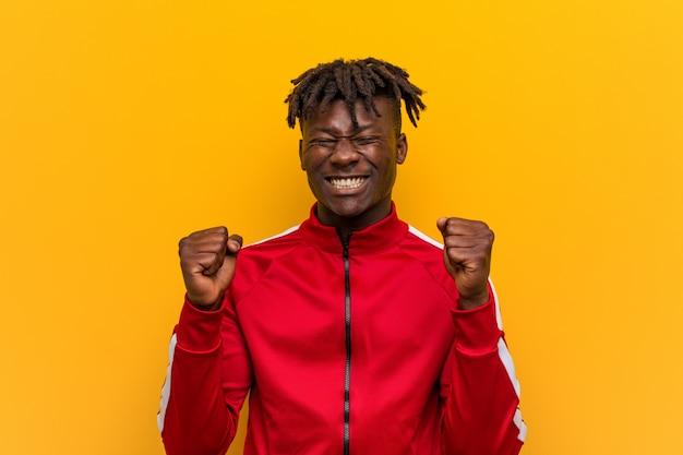 Homem negro novo da aptidão que levanta o punho, sentindo feliz e bem sucedido. conceito de vitória.