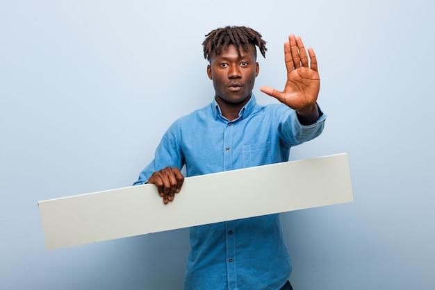 Homem negro novo do rasta que guarda um cartaz que está com a mão estendido que mostra o sinal da parada, impedindo-o.