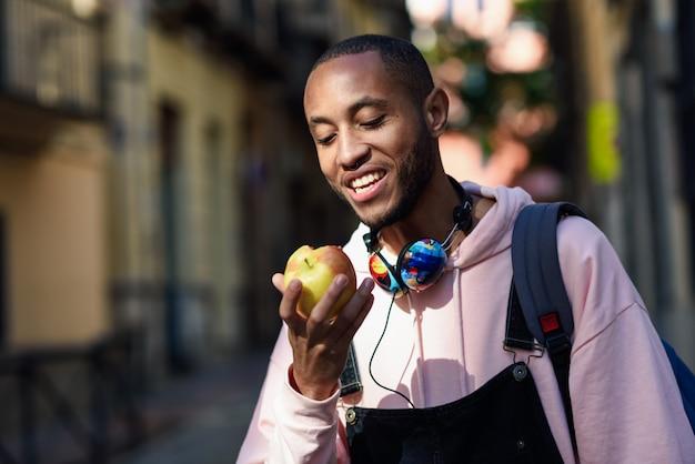 Homem negro novo que come uma maçã que anda abaixo da rua.