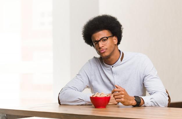 Homem negro novo que tem um café da manhã que cruza os braços relaxados