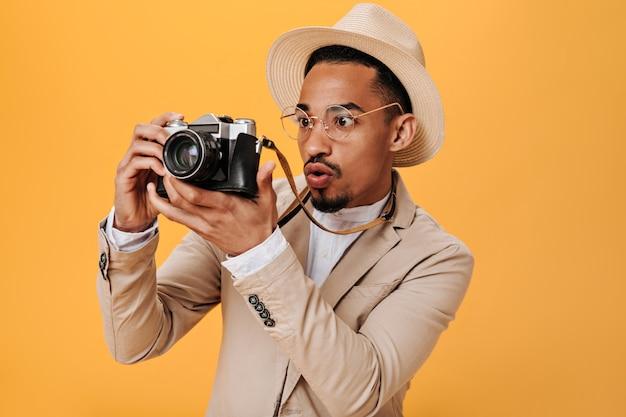 Homem negro olhando para uma câmera retro com interesse