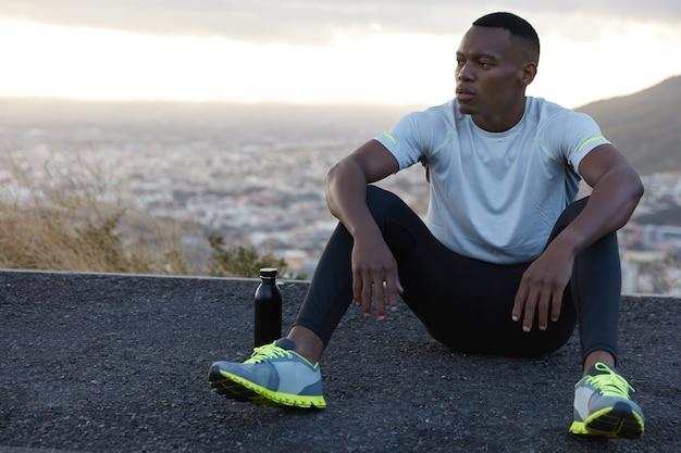 Homem negro pensativo e despreocupado apóia as mãos nos joelhos, descansa no asfalto, bebe água doce, respira ar, gosta da solidão, maquetes sobre vista panorâmica desfocada com espaço de cópia para sua publicidade