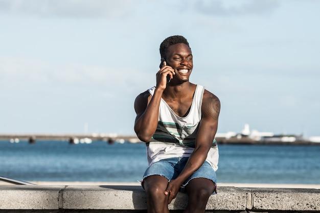 Homem negro positivo falando em smartphone em frente ao mar no verão