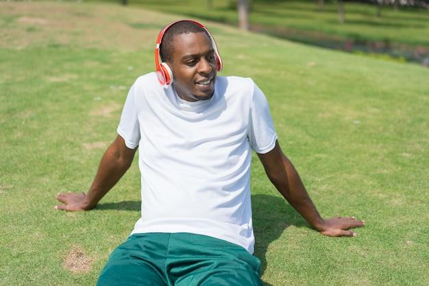 Homem negro positivo relaxante no parque e ouvir música com fones de ouvido sem fio.