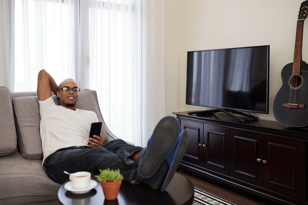Homem negro preguiçoso relaxando no sofá em casa e verificando mensagens de texto e mídias sociais no smartphone