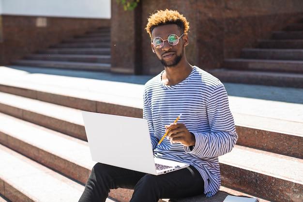 Homem negro que estuda na escada