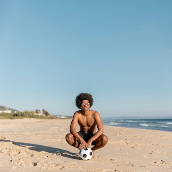Homem negro relaxado com bola na praia