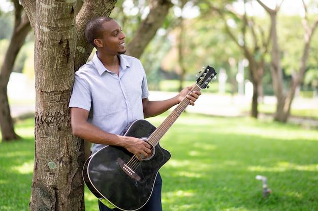 Homem negro relaxado tocando violão e encostado na árvore