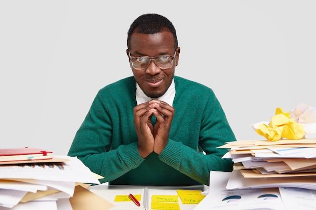 Homem negro satisfeito tem intenção de fazer algo, mantém as mãos em gestos intrigantes, usa óculos transparentes, planeja o trabalho do projeto, decide o que fazer a seguir