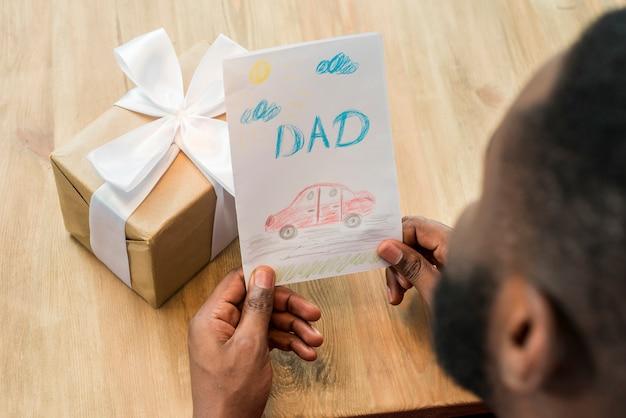 Homem negro, segurando o cartão com a inscrição do pai
