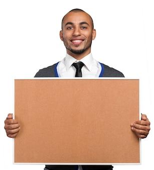 Homem negro segurando uma placa de cortiça