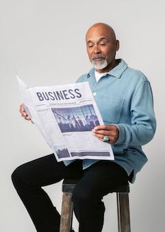 Homem negro sentado em um banquinho lendo jornal