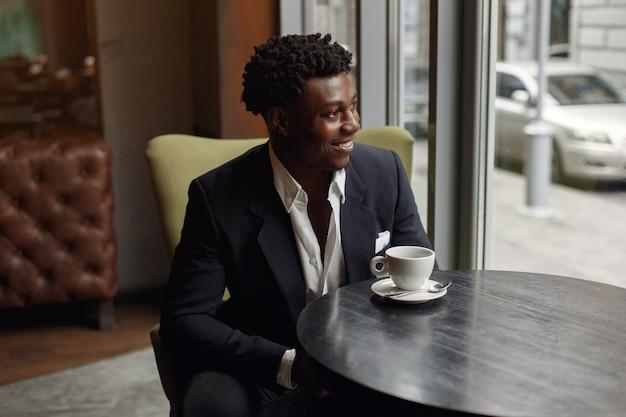 Homem negro sentado em um café e tomando um café