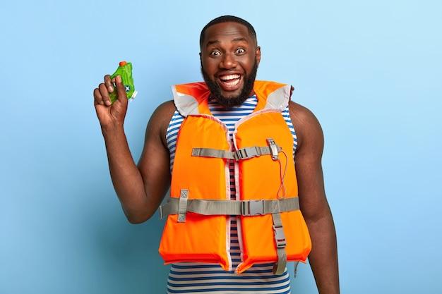 Homem negro sorridente e feliz com uma pequena pistola d'água de brinquedo na mão