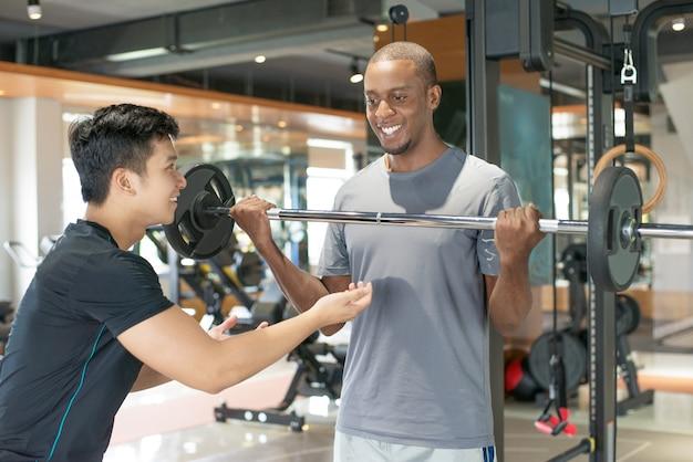 Homem negro sorridente, levantando a barra com personal trainer