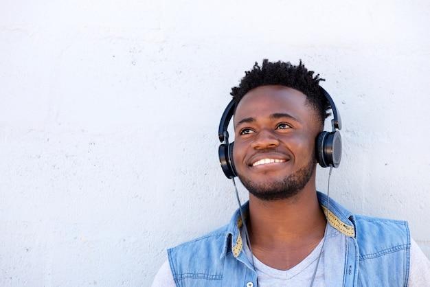 Homem negro sorridente ouvindo música com fones de ouvido