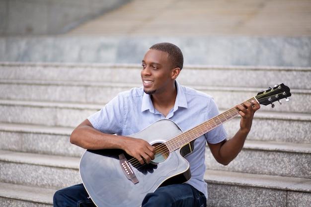 Homem negro sorridente tocando violão e sentado na escada