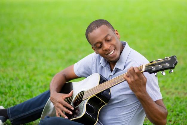Homem negro sorridente tocando violão e sentado na grama