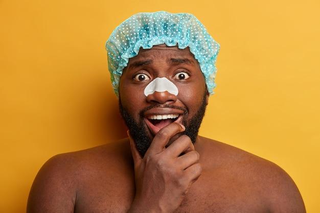 Homem negro surpreso de barba segurando o queixo e usando tira de limpeza no nariz