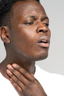 Homem negro toca dedos de garganta inflamada, glândula tireóide