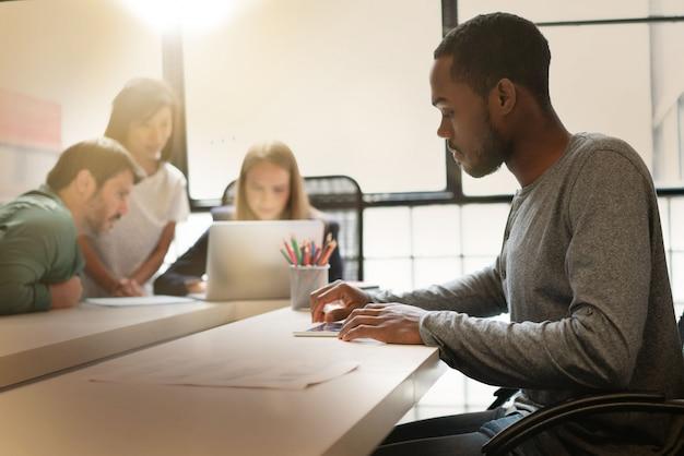 Homem negro, trabalhando no espaço de escritório moderno com colegas de trabalho