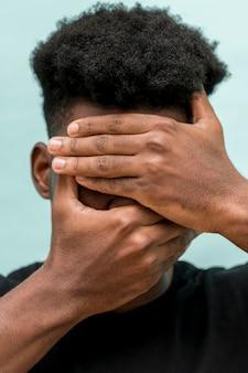 Homem negro triste com as mãos cobrindo o rosto