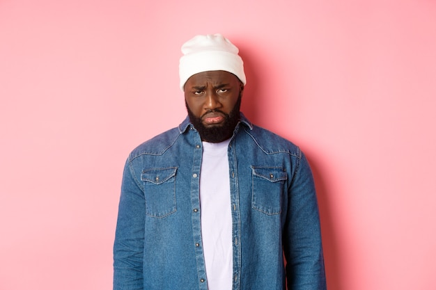 Homem negro triste e desapontado, mal-humorado e choramingando, olhando para a câmera com uma careta ofendida, em pé sobre um fundo rosa