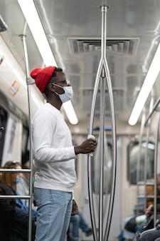 Homem negro usa máscara facial no trem do metrô durante a pandemia de covid19 segurando o corrimão através do guardanapo