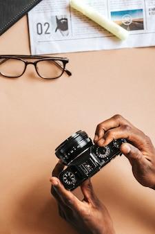 Homem negro usando câmera analógica