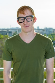 Homem nerd com cabelo vermelho e óculos contra a vista da cidade