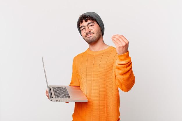 Homem nerd com computador fazendo capice ou gesto de dinheiro, mandando você pagar suas dívidas!