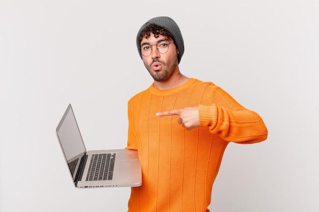 Homem nerd com computador parecendo surpreso e descrente, apontando para um objeto ao lado e dizendo uau, inacreditável