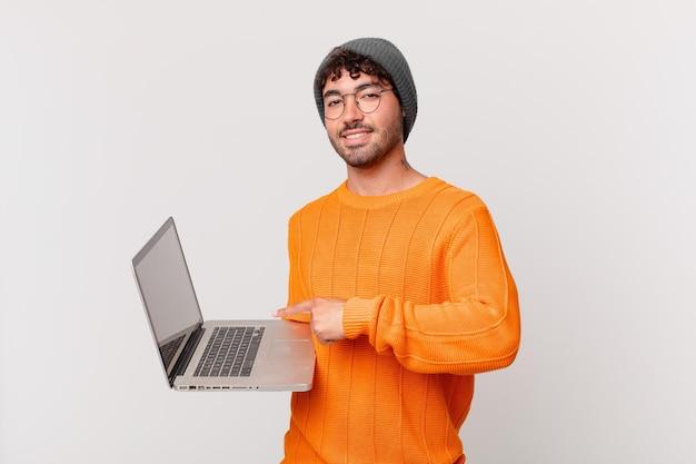 Homem nerd com computador sorrindo alegremente, sentindo-se feliz e apontando para o lado e para cima, mostrando o objeto no espaço da cópia